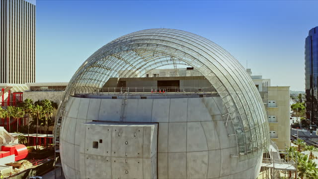 ws aerial across glass-domed theater building newly constructed for the academy museum of motion pictures climbing higher and ending with birds eye view of miracle mile district - academy of motion picture arts and sciences stock videos & royalty-free footage