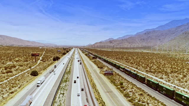 ws aerial across interstate 10 california freeway as mile-long freight train carrying double stacked containers runs parallel to the highway and a frontage road traveling east towards coachella valley - interstate 10 stock videos & royalty-free footage
