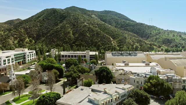aerial across midwestern town square and church on studio backlot looking west towards mountains - studio shot stock videos & royalty-free footage