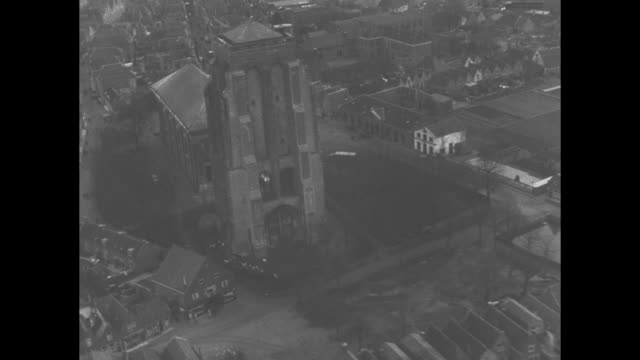 vidéos et rushes de aerial across netherlands villages and towns, buildings surrounded by water / cathedral in center of flooded town / fly over windmill with helicopter... - pays bas