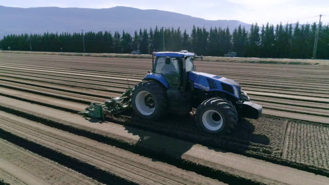 aerial action - blue tractor and cultivator preparing a field in the springtime - sowing stock videos & royalty-free footage