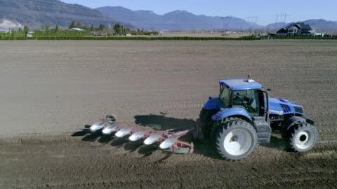 vídeos y material grabado en eventos de stock de aerial action - blue tractor and plough in the springtime - campo arado