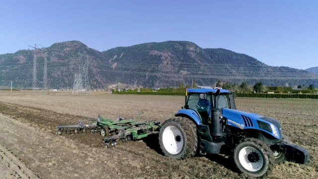 aerial action - preparing the fields with a disc harrow - plowed field stock videos & royalty-free footage
