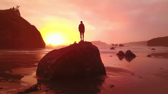 aerial: active man on rock admiring amazing sunset - esplorazione video stock e b–roll