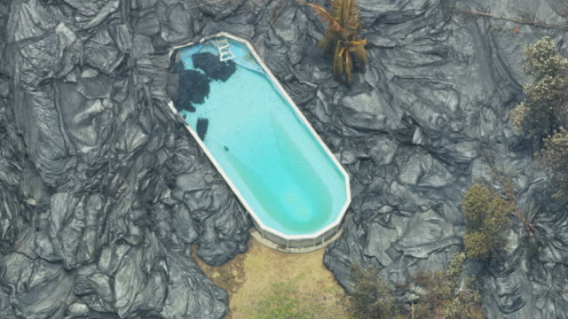 aerial active rock lava solidifying around swimming pool - big island hawaii islands stock videos & royalty-free footage