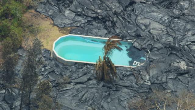 vídeos y material grabado en eventos de stock de aerial active rock lava solidifying around swimming pool - 2018