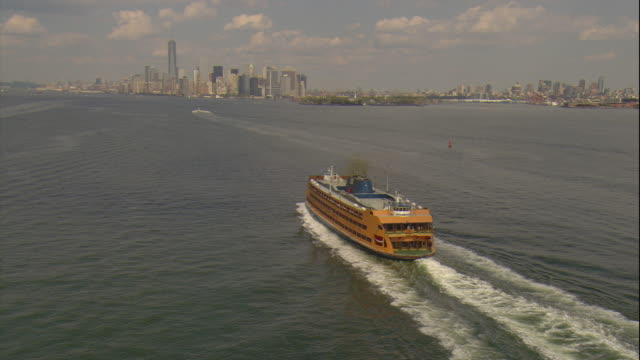 aerial -afternoon mcu orbiting shot of a staten island ferry boat to reveal the lower manhattan skyline and freedom tower behind. - staten island stock videos and b-roll footage