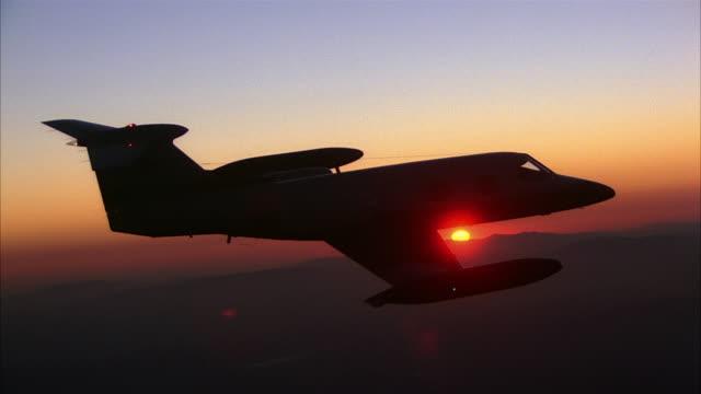 aerial airplane flying with sunset in background - flugzeug in der luft stock-videos und b-roll-filmmaterial