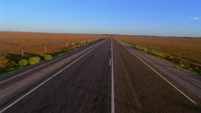 stockvideo's en b-roll-footage met aerial along deserted highway / up to and over man walking on highway - tweebaansweg