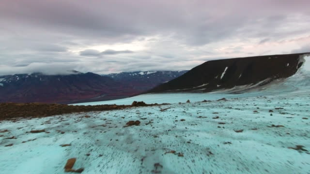 Aerial along icy slope in Arctic Circle