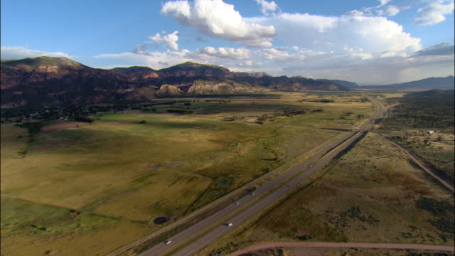 aerial along interstate 15/ across farmland to mountains/ utah - utah stock videos & royalty-free footage