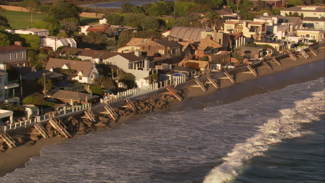 Aerial TS MS along residential beachfront homes / Malibu, California, United States.
