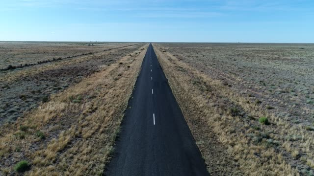 vidéos et rushes de aerial along road in desert - infini