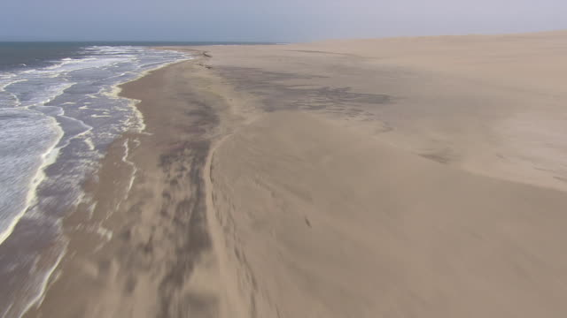 vídeos de stock e filmes b-roll de aerial along the coastline in namibia along the edge of the water and sand - aerial or drone pov or scenics or nature or cityscape