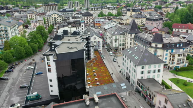 vidéos et rushes de aerial: amazing lush green mountains with snowy peaks over scenic town - chamonix, france - panning