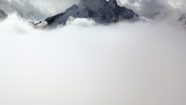 aerial: amazing snowy mountain peak among thick clouds - mount blanc, france - thick stock videos & royalty-free footage