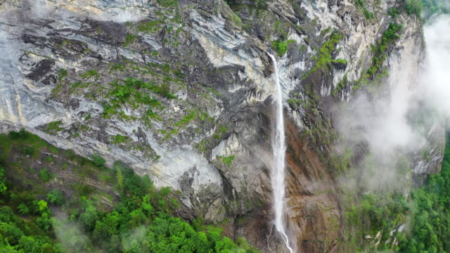 vidéos et rushes de aerial: amazing waterfall on high cliff wall over lush green forest - chamonix, france - torrent