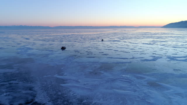 aerial: amphibious vehicles floating on frozen lake baikal against blue and orange sky - hovercraft stock videos & royalty-free footage