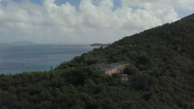 aerial: angling around house with hurricane damage on island in the caribbean in st. croix, us virgin islands - anchored stock videos & royalty-free footage