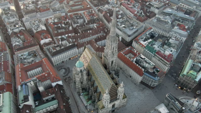 aerial: angling down over st. stephen's cathedral and rooftops of vienna, austria - austria video stock e b–roll