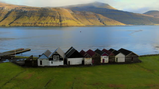 aerial antique shacks in a row at coast of lake, drone turn to view mountains, streymoy island, faroe islands - barn stock videos & royalty-free footage