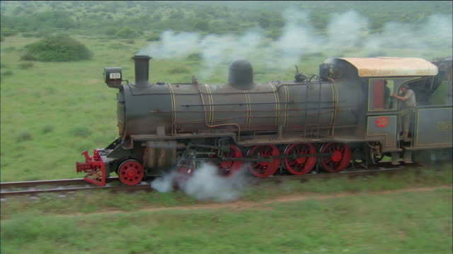 aerial antique steam train traveling along tracks - dampf stock-videos und b-roll-filmmaterial