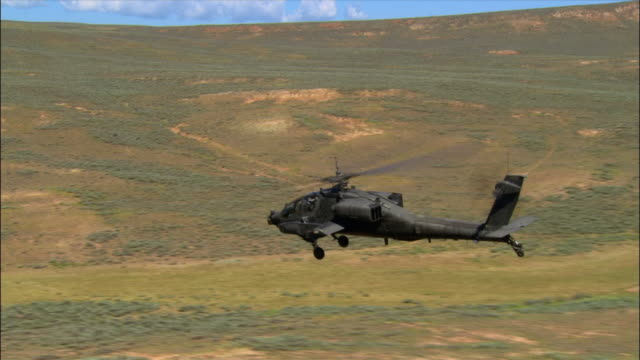 aerial apache helicopter flying low over rural landscape / evanston, wyoming - アパッチヘリコプター点の映像素材/bロール
