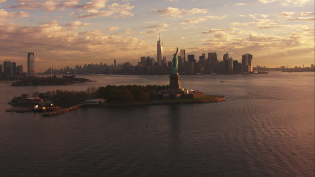 aerial approach liberty island and downtown manhattan sunset - freiheitsstatue stock-videos und b-roll-filmmaterial