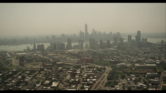 aerial approach to hazy downtown manhattan over jersey city - ジャージーシティ点の映像素材/bロール