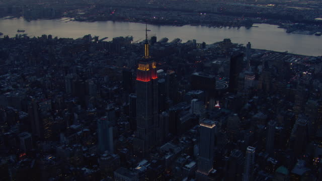 aerial approach to the empire state building at dusk. the skyscraper is one of the tallest buildings in new york city and one of its most famous landmarks. - 20世紀のスタイル点の映像素材/bロール