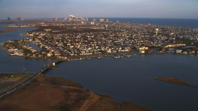 vidéos et rushes de aerial approach towards atlantic city over marshlands into margate city. shot in 2011. - allée couverte de planches