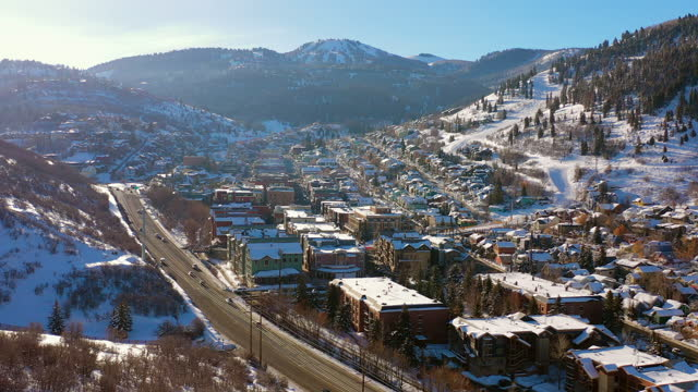 aerial approaching a residential neighborhood in a snowy mountain ski town with quiet streets and bright morning sunlight - park city, utah - park city stock videos & royalty-free footage