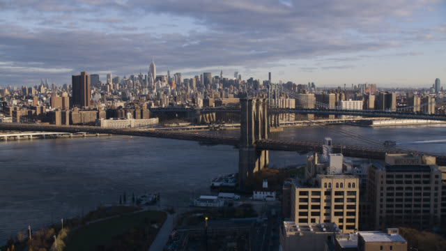aerial approaching brooklyn bridge. east river. new york city skylines with skyscrapers and high rise office or apartment buildings. - brooklyn bridge stock videos & royalty-free footage