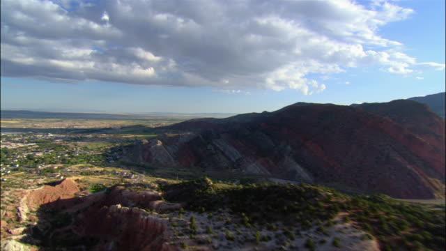 aerial approaching red rock hills/ suburban houses and horizon under clouds/ cedar city, utah - utah stock videos & royalty-free footage