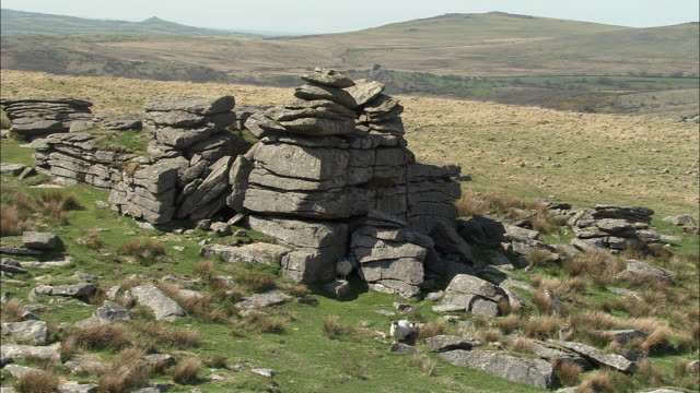Aerial around exposed granite tor, Dartmoor, UK