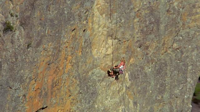 aerial around female mountain climber descending - rock climbing stock videos & royalty-free footage