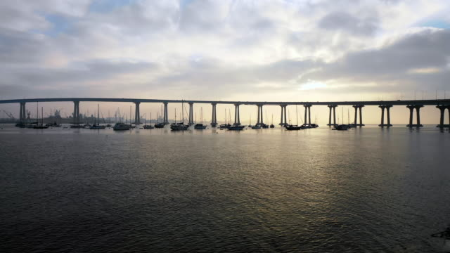 stockvideo's en b-roll-footage met aerial ascend: bridge over river filled with boats on cloudy day in san diego, united states of america - san diego