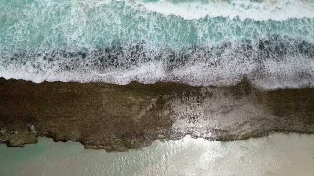 aerial ascend: bright blue ocean with waves crashing on shore - esperance, australia - stone material stock videos & royalty-free footage