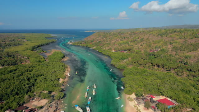 aerial ascend: bright blue water between two islands, boats, houses - nusa ceningan, bali - town stock videos & royalty-free footage