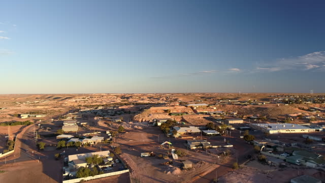 aerial ascend: buildings and cars on large, flat plain with blue sky - uluru, australia - エアーズロック点の映像素材/bロール