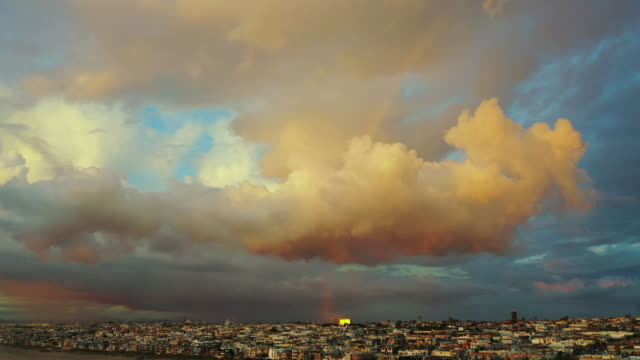 aerial ascend: colorful rainbow in cloudy sky over town - manhattan beach, california - arcobaleno video stock e b–roll