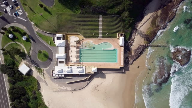 aerial ascend: empty pool on edge of sandy shore and green ocean waves, wollongong, australia - standing water stock videos & royalty-free footage