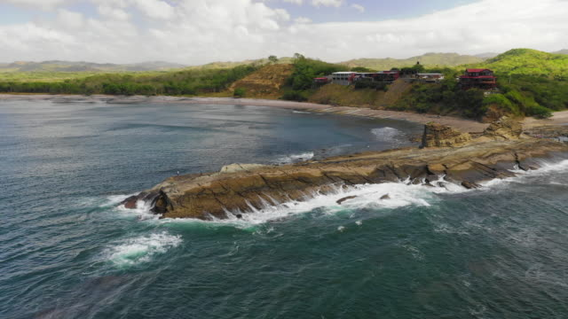 aerial ascend: large rock in ocean shallows leading to grassy shore - el gigante, nicaragua - nicaragua stock videos & royalty-free footage