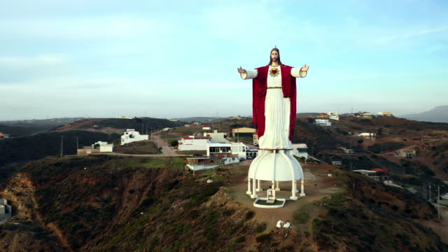 aerial ascend right: large jesus statue overlooking town in large valley in baja malibu, mexico - town stock videos & royalty-free footage