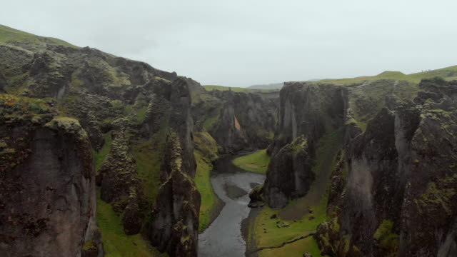 aerial ascend: small river at bottom of tall, rocky valley in fjaorargljufur, iceland - geology stock videos & royalty-free footage