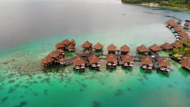aerial ascend: tropical vacation homes in ocean in bora bora, french polynesia - bora bora aerial stock videos and b-roll footage