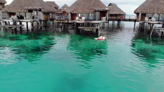 aerial ascend: woman floating next to tropical hut in gorgeous ocean in bora bora, french polynesia - bora bora aerial stock videos and b-roll footage