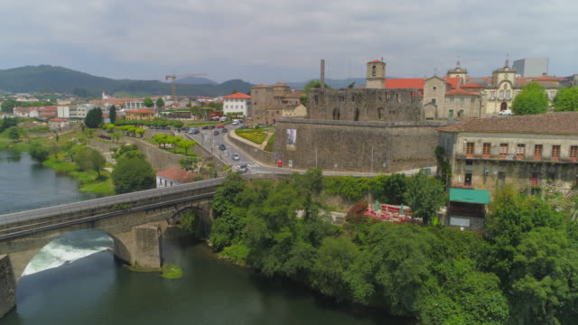 aerial ascending: palace of the dukes on a sunny day overlooking cavado river and busy bridge of barcelos - barcelos, portugal - peerage title stock videos & royalty-free footage