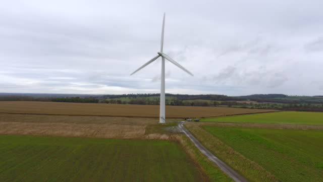 aerial ascending view of a single wind turbine against farmland - energy efficient stock videos & royalty-free footage