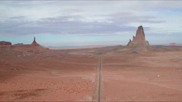 aerial ascend/pan down: desert plain with car driving down center in monument valley, ut - cross section stock videos & royalty-free footage